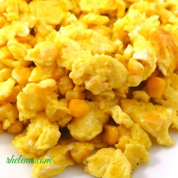 A closeup of scrambled eggs and corn.
