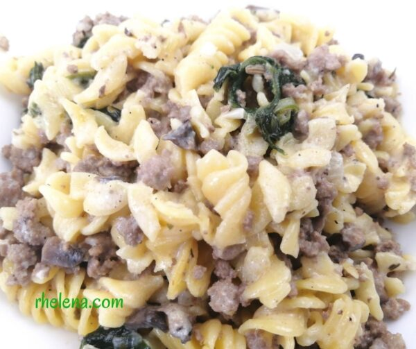 A bowl of a creamy pasta with Italian sausage, ground beef, spinach and mushrooms.