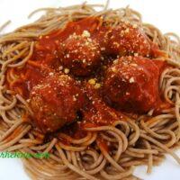 Meatballs shown on einkown spaghetti.
